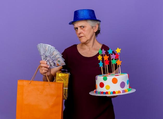 Clueless oudere vrouw met feestmuts houdt geld geschenkdoos papieren boodschappentas en verjaardagstaart geïsoleerd op paarse muur met kopie ruimte