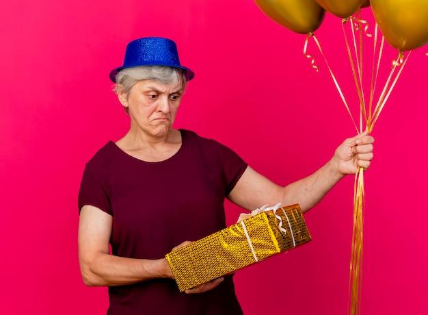 Clueless oudere vrouw met feestmuts houdt helium ballonnen en kijkt naar geschenkdoos op roze