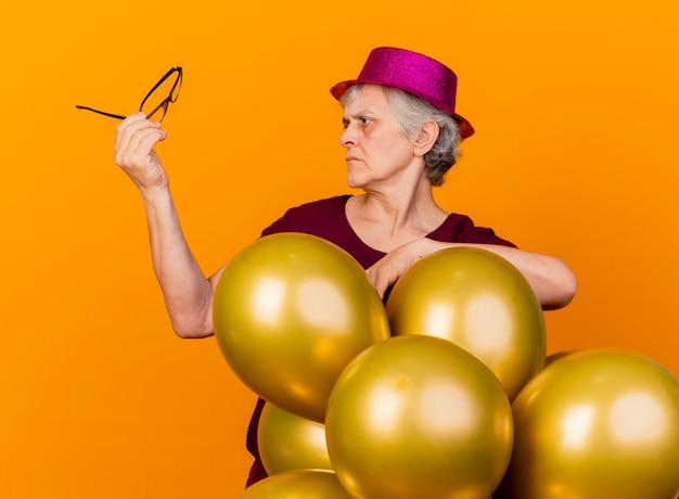 Clueless oudere vrouw met feestmuts staat met helium ballonnen houden en kijken naar optische bril geïsoleerd op oranje muur