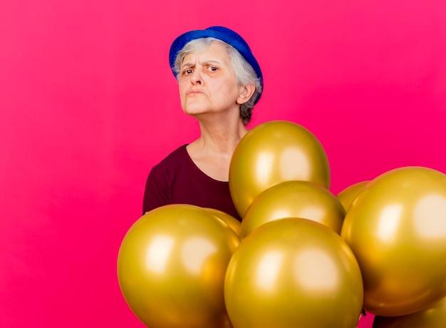 Clueless oudere vrouw met feestmuts staat met helium ballonnen op roze