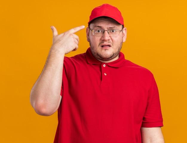 Clueless overgewicht jonge bezorger in optische bril wijzend op zijn pet geïsoleerd op oranje muur met kopie ruimte