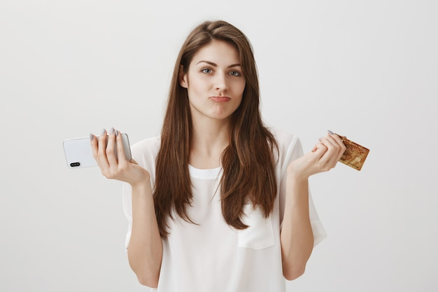 Clueless schattig meisje schouderophalend met creditcard en mobiele telefoon