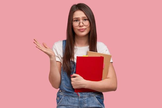 Clueless schoolmeisje spreidt palm, gekleed in een casual wit t-shirt en overall, draagt een optische bril, draagt een notitieblok met de nodige notities