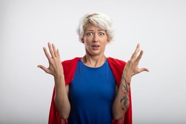 Clueless supervrouw met rode cape staat met opgeheven handen geïsoleerd op een witte muur