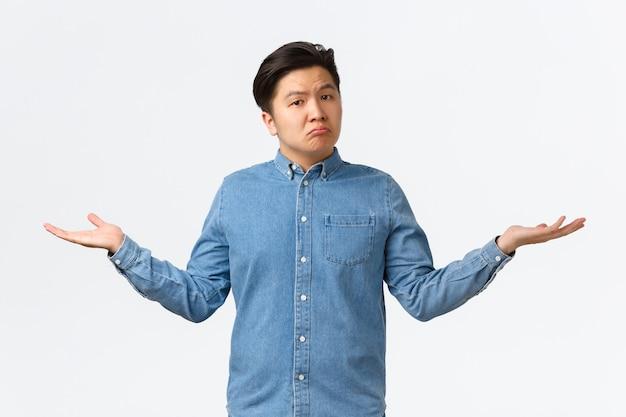 Clueless trieste aziatische jonge kerel weet niets, spreidt handen zijwaarts en haalt onbewust zijn schouders op, staat geen idee, kan het niet begrijpen, staat besluiteloos over een witte achtergrond zonder antwoorden.