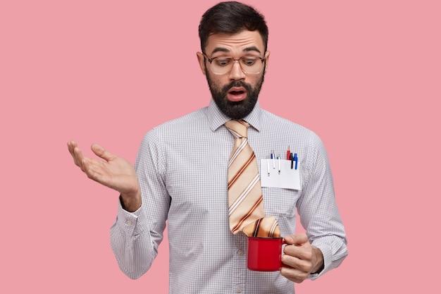 Clueless verrast man met dikke haren, steekt hand op, kijkt verontwaardigd naar beker met stropdas, gekleed in formele kleding