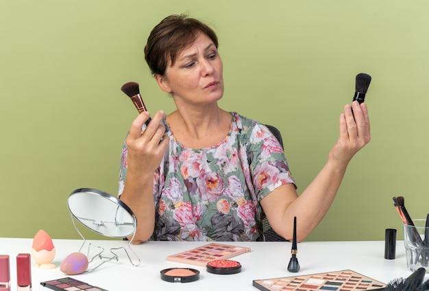 Clueless volwassen blanke vrouw zittend aan tafel met make-up tools houden en kijken naar make-up borstels geïsoleerd op olijf groene muur met kopie ruimte