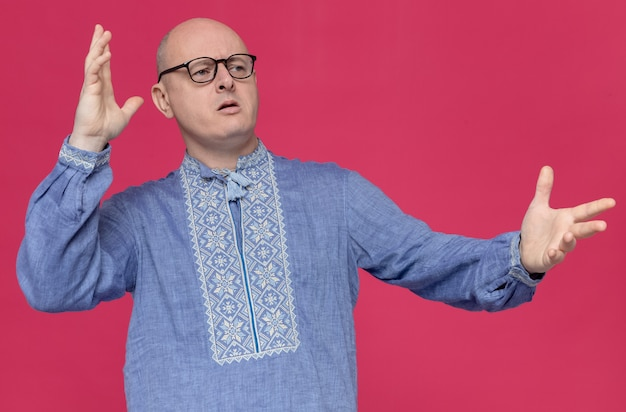 Clueless volwassen man in blauw shirt met een bril die met opgeheven handen naar de zijkant kijkt