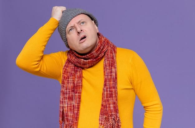 Clueless volwassen man met sjaal om zijn nek die een wintermuts vasthoudt en omhoog kijkt