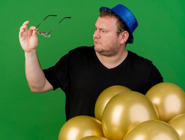 Clueless volwassen slavische man houdt en kijkt naar een optische bril met een blauwe feesthoed die met heliumballonnen staat