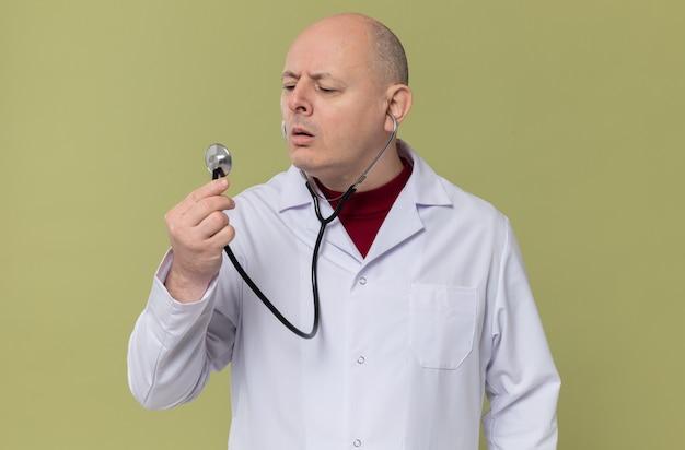 Clueless volwassen slavische man in doktersuniform die stethoscoop kijkt en vasthoudt