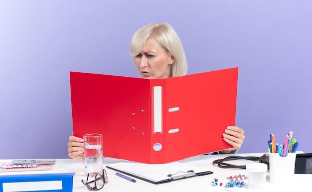 Clueless volwassen slavische vrouwelijke arts in medische gewaad met stethoscoop zittend aan een bureau met office tools houden en kijken naar bestandsmap geïsoleerd op paarse muur met kopie ruimte