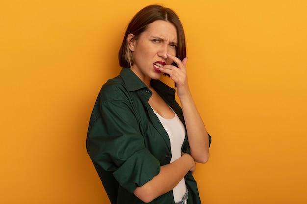 Clueless vrij blanke vrouw bijt vinger en kijkt naar de camera op oranje