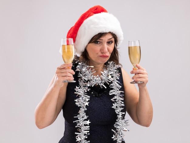 Clueless vrouw van middelbare leeftijd dragen kerstmuts en klatergoud slinger rond nek houden twee glazen champagne kijken camera geïsoleerd op witte achtergrond