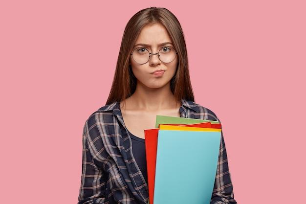 Clueless vrouwelijke lezer tuiten lippen met twijfelachtige uitdrukking, heeft sombere uitdrukking,