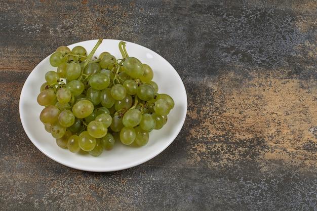 Cluster van groene druiven op witte plaat.