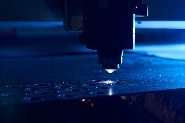 Cnc lasersnijden van metaal close up, moderne industriële technologie. kleine scherptediepte