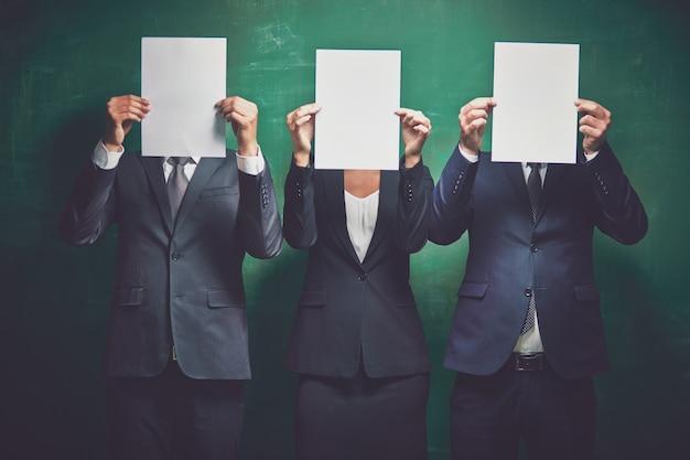 Co-werknemers het verbergen van hun gezichten met lege vellen