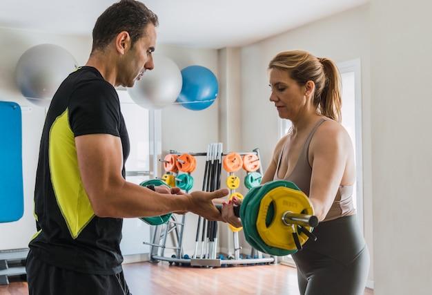 Coach die een vrouw leert hoe ze gewichten moet doen in een sportschool