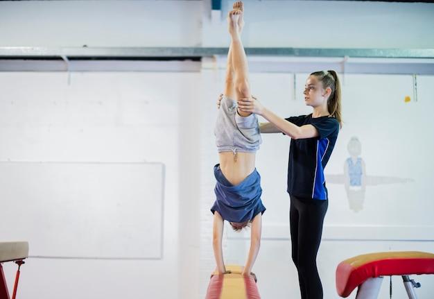 Coach die jonge turner opleidt om een handstand op een evenwichtsbalk te doen