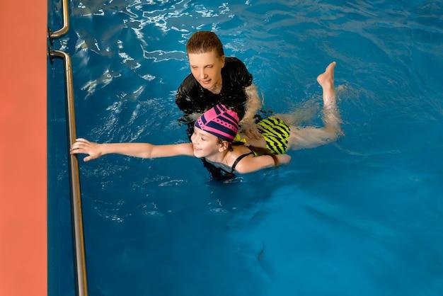 Coach die kind in binnenzwembad leert zwemmen en duiken