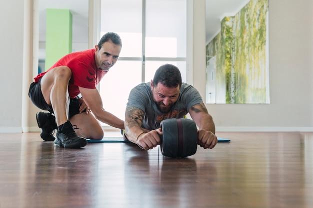Coach helpt een man om te oefenen met een buikspierroller in een sportschool