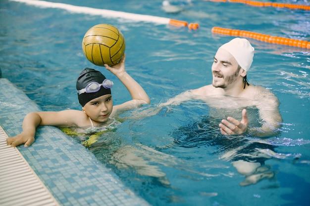 Coach leert kind in overdekt zwembad hoe te zwemmen en duiken. zwemles, ontwikkeling van kinderen.