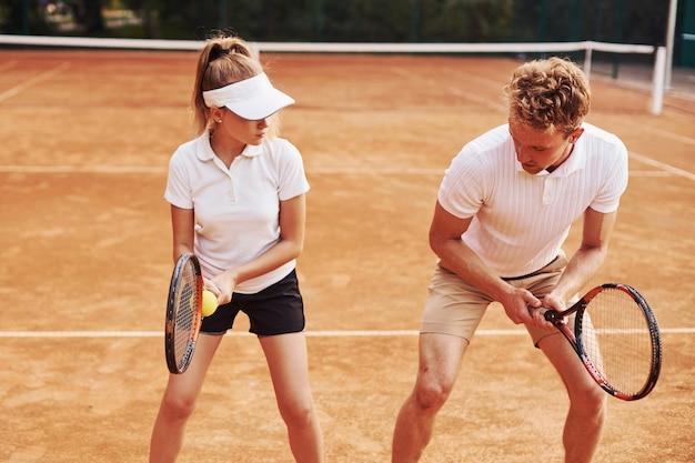Coach lesgeven vrouwelijke student tennisspel in de rechtbank buitenshuis.