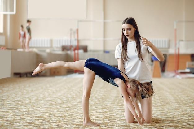 Coach met student. meisjes gymnasten, voert verschillende gymnastische oefeningen uit en springt. kind en sport, een gezonde levensstijl.