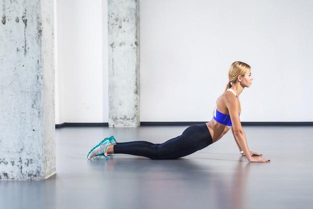Cobra, pilates of yogahouding. vrouw gaan liggen, oefening doen. studio-opname, geïsoleerd op een grijze achtergrond