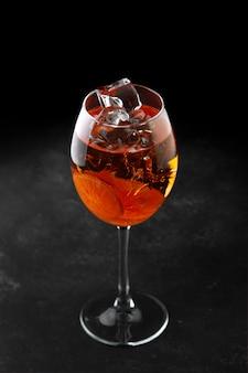 Cocktail aperol spuit met ijs op een zwarte achtergrond Premium Foto