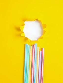 Cocktail buizen op een gele papieren tafel met een gescheurd gat minimalism zomer concept