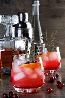 Cocktail cranberry sinaasappel bourbon smash met een pittige hint van tijm