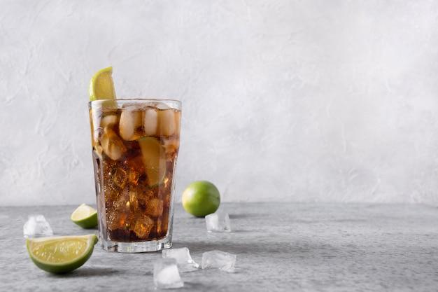 Cocktail cuba libre of long island ijsthee met rom, cola, limoen en ijs in glas op grijze stenen tafel.