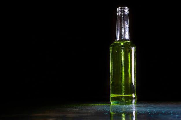 Cocktail geel drankje in fles koud op tafel / donkere stijl en categorie drinken eten