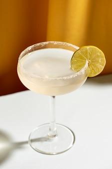 Cocktail gegarneerd met limoen op witte tafel
