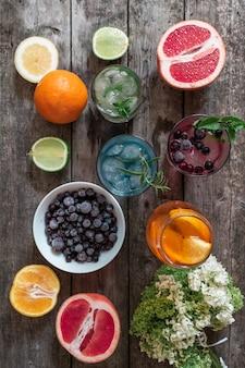 Cocktail gin tonic, mojito en aperol spritz met munt, ijs, limoen, bessen, grapefruit en sinaasappel op de houten achtergrond.