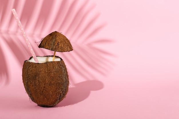 Cocktail in een open kokosnoot en de schaduw van palmbladen op roze. zomerstemming, oogsten.