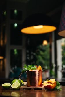 Cocktail in ijzeren mok met perzik, limoenmunt en gember