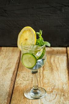 Cocktail komkommer water met citroen en munt in een glas op een houten tafel op een zwarte achtergrond.