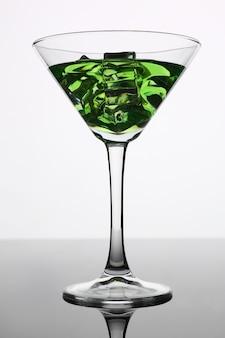 Cocktail met alcohol in groene kleur en ijsblokjes