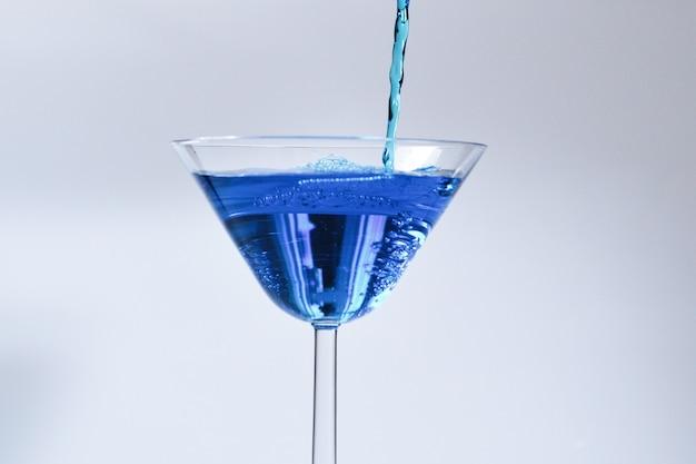 Cocktail met blauwe vloeistof in glas. glas met blauw water gieten met vloeistof met spatten en druppels. martiniglas vullen met alcohol met spatten op witte achtergrond. verfrissend drankje concept.