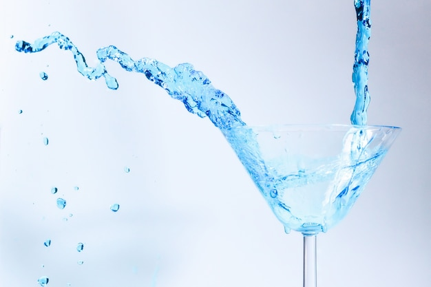 Cocktail met blauwe vloeistof in glas. glas met blauw water gieten met vloeistof met spatten en druppels.