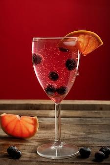 Cocktail met bosbessen en druivenfruit op een rustieke houten tafel met een rode muur erachter