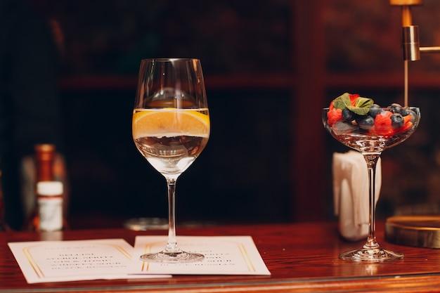 Cocktail met citroen in glas op barbureau met menu