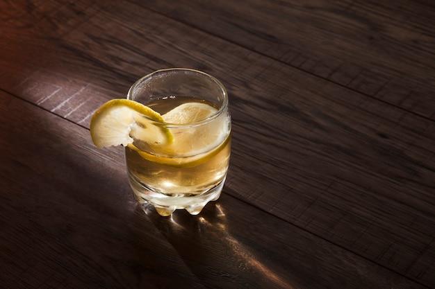 Cocktail met citroen op de houten lijst