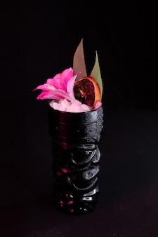Cocktail met een bloem in een etnisch glas cocktaillijst cocktailmenu zwarte achtergrond