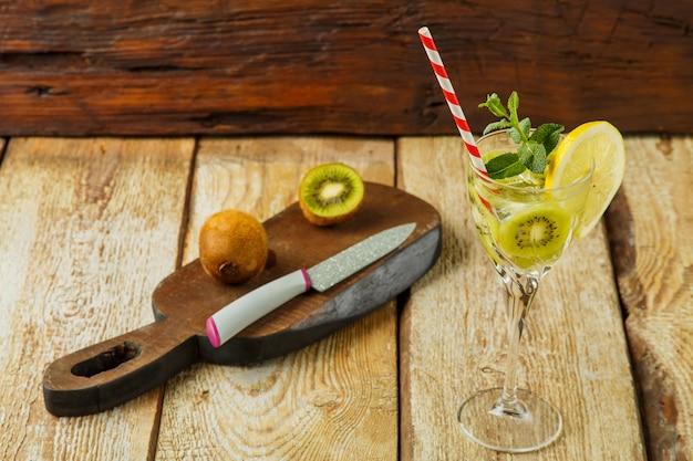 Cocktail met kiwi-munt en citroen in een glas op een houten tafel naast citroen en kiwi op een bord. horizontale foto