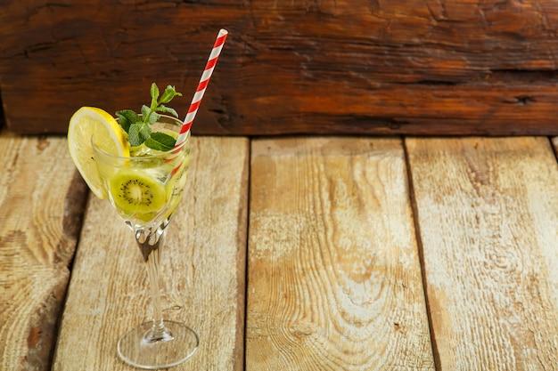Cocktail met kiwimunt en citroen in een glas op een houten tafel. ruimte kopiëren. horizontale foto