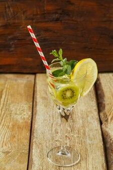 Cocktail met kiwimunt en citroen in een glas op een houten tafel